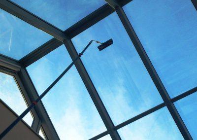 Mycie okien świetlika od wewnątrz przy pomocy szczotek teleskopowych